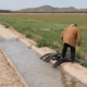 Man standing near irrigation ditch on the Gila River Indian Community in Arizona